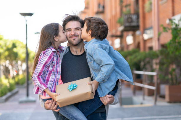 loving son and daughter kissing daddy on the cheek while he carries them both with a present for father's day - fathers day stock photos and pictures