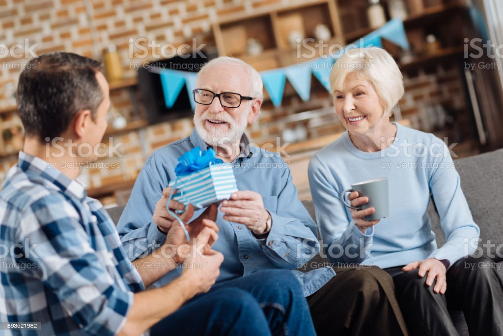 Loving Son Giving Birthday Present To His Elderly Father