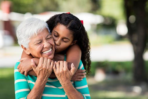 istock Loving teen girl embracing and kissing grandmother 963933856