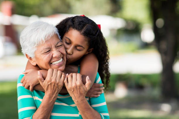 Loving teen girl embracing and kissing grandmother A loving teen girl embracing and kissing her happy grandmother from behind and holding each other outdoors. 65 69 years stock pictures, royalty-free photos & images