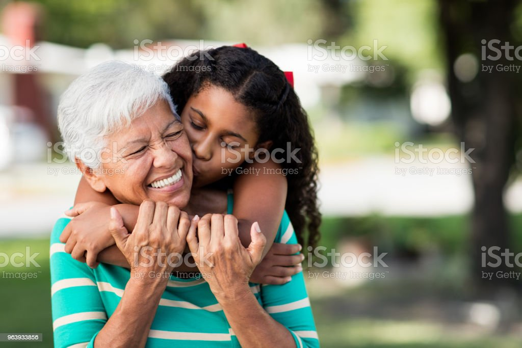 Loving teen girl embracing and kissing grandmother stock photo
