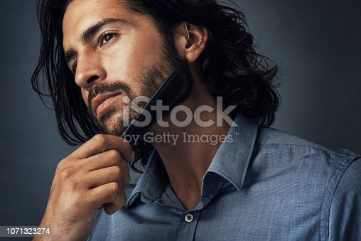 Studio shot of a handsome young man combing his beard against a grey background