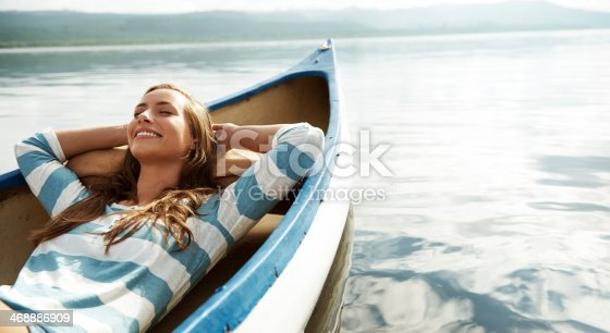 An attractive young woman relaxing and daydreaming in a canoe
