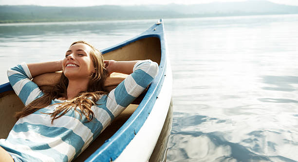 Loving the fresh air An attractive young woman relaxing and daydreaming in a canoe tranquil scene stock pictures, royalty-free photos & images