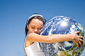 little girl holding globe in her arms, eyes closed, against blue sky