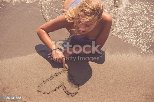 High angle view of a young woman lying down on the beach while drawing a heart on the sand.