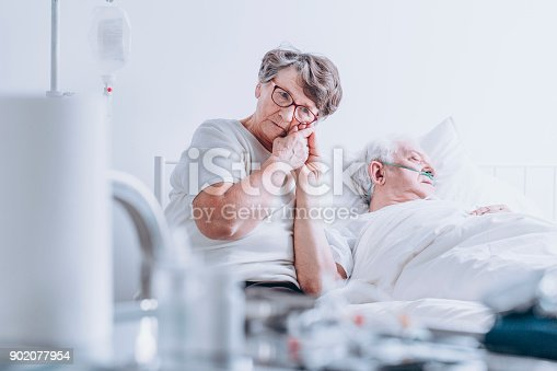 902077950istockphoto Loving wife at hospital bed 902077954