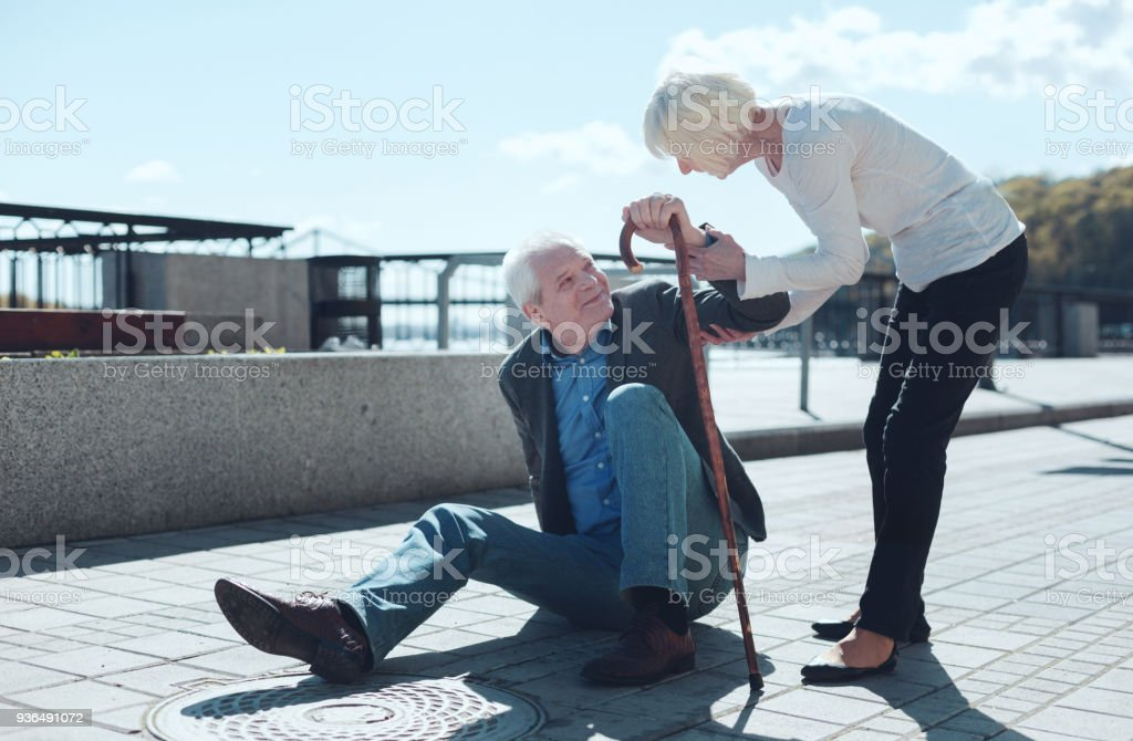 Liebevolle Frau helfen älteren Mann aufzustehen – Foto