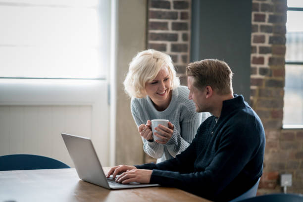 Loving woman bringing her partner a hot cup of coffee while he is working on his laptop both smiling stock photo