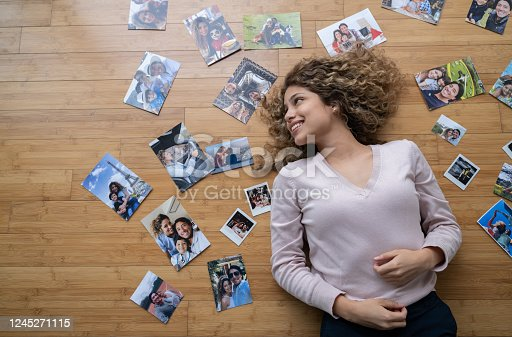 Loving young woman lying on the floor surrounded by pictures of her family and looking happy