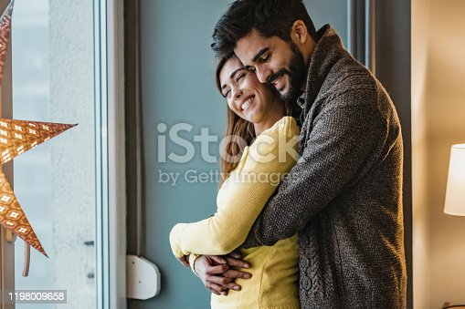 Portrait of young couple at home during winter. They are having a romantic moment