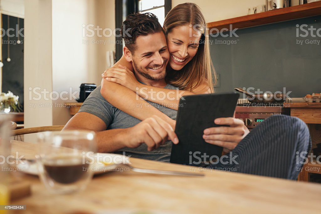 Loving young couple catching up on social media smiling stock photo