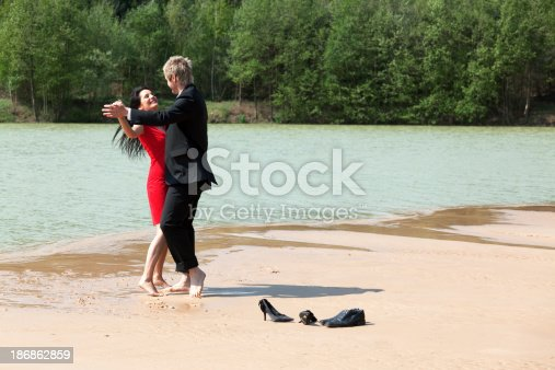 Loving young couple dancing barefooted on sand lakeside.Please also have a look at my private lightbox: