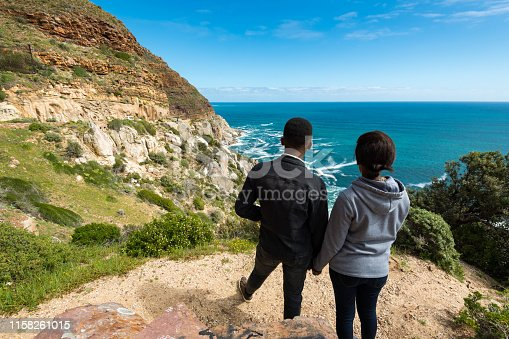 Rear view of young couple enjoying sea view. Loving man and woman are spending quality time together. They are enjoying their weekend.
