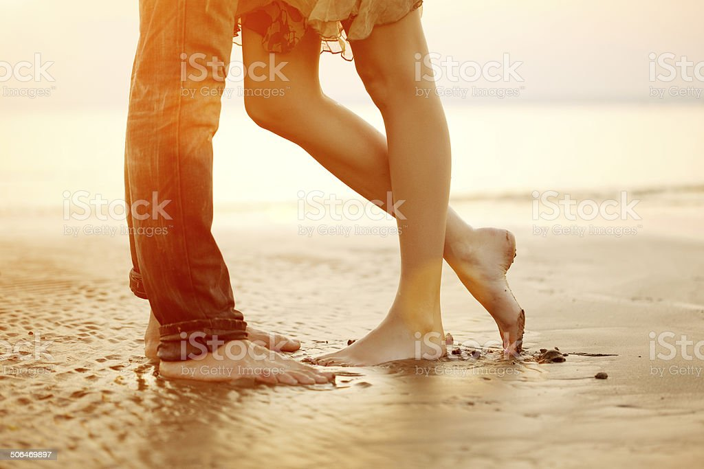 Loving young couple hugging, kissing on the beach at sunset stock photo
