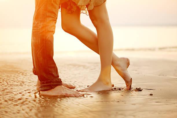liebevolle junge paar umarmen und küssen am strand bei sonnenuntergang - romantische strand fotos stock-fotos und bilder