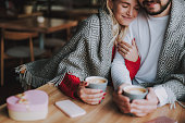 istock Loving young couple in warm blankets cuddling at cafe 1086628628