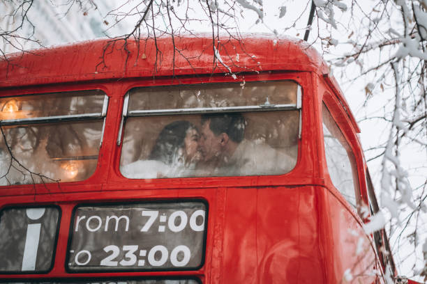 Loving young couple kissing in the red bus, enjoy each other stock photo