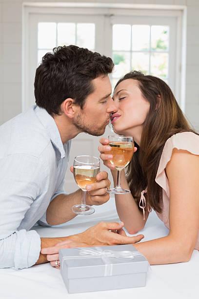 amorevole giovane coppia baciare con bicchieri di vino - brunette woman eyeglasses kiss man foto e immagini stock