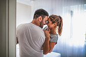 Handsome man in white T-shirt carrying young attractive woman while spending free time at home. Loving young hipster couple relaxing at home and kissing. View from another room through the doorway