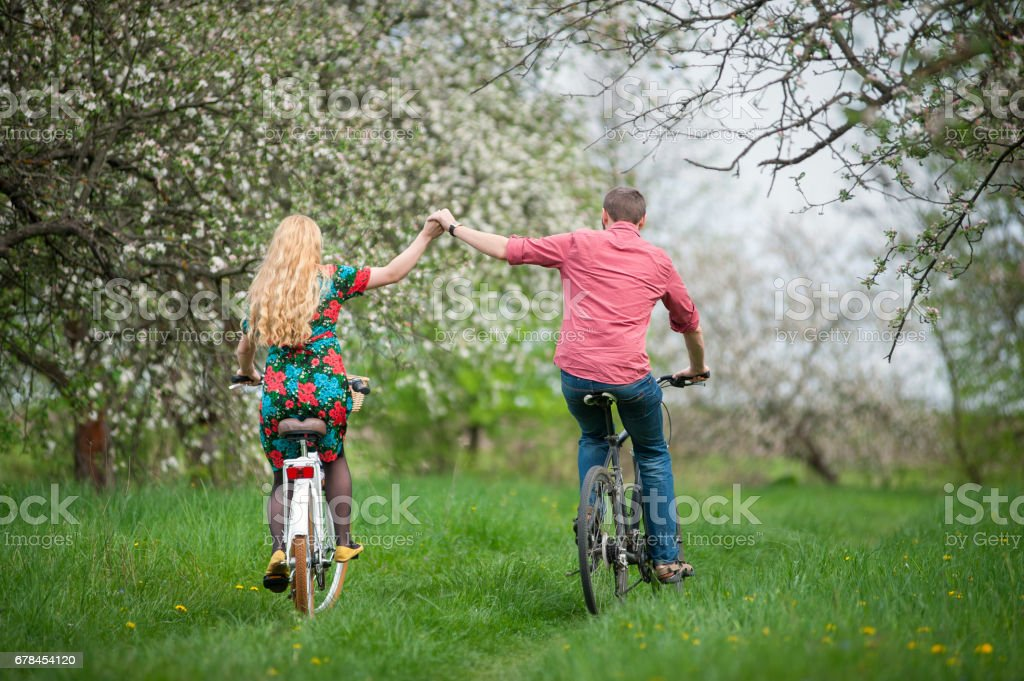 Loving young couple riding bicycles in the spring garden royalty-free stock photo