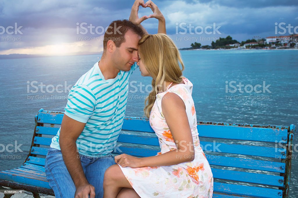 Loving young couple sitting on a dock. Storm in background stock photo