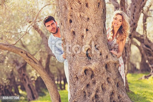 istock Loving young couple standing by trees at olive trees 838467398