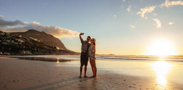 liebevolles junges paar beim selfie am strand - schönen abend bilder stock-fotos und bilder