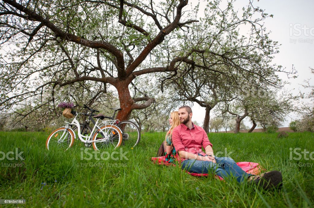 Loving young couple with bicycles in spring garden royalty-free stock photo