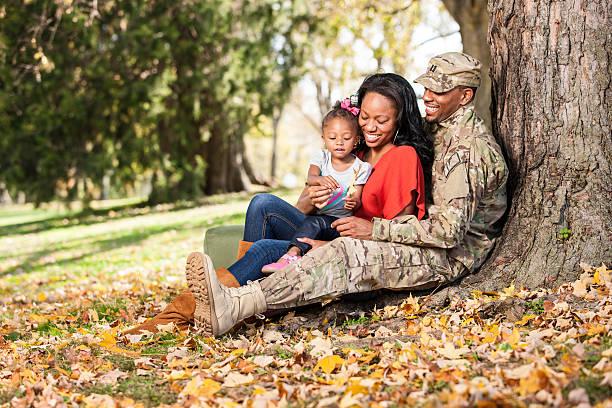 Liebevolle junge Familie im Park im Military – Foto