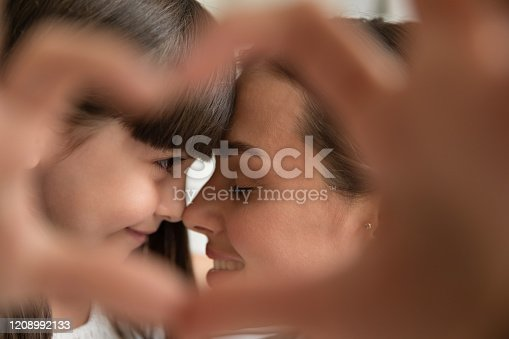 Close up of young mother and little cute preschooler daughter cuddle look in eyes share tender close moment showing heart sign, caring mom and small girl child embrace show love and bonding