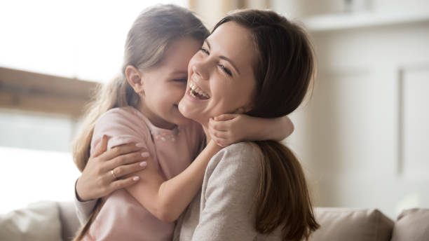 Loving young mother laughing embracing smiling cute funny kid girl stock photo