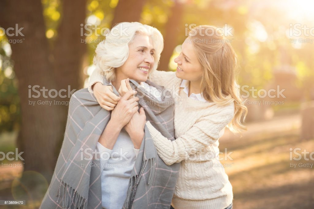 Loving young woman covering old mother with blanket outdoors stock photo