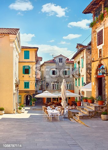 Lovran, Croatia. Central area of ancient old town with vintage buildings and cosy street cafes and restaurants. Sunny summer day. Urban landscape of historical centre.