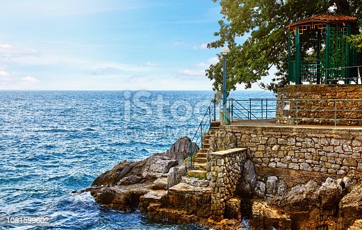 Lovran, Croatia. Rocky stone coastline with big rocks pavilion in shade of tree and stairs to Adriatic Sea. Blue waves sky clouds above horizon.