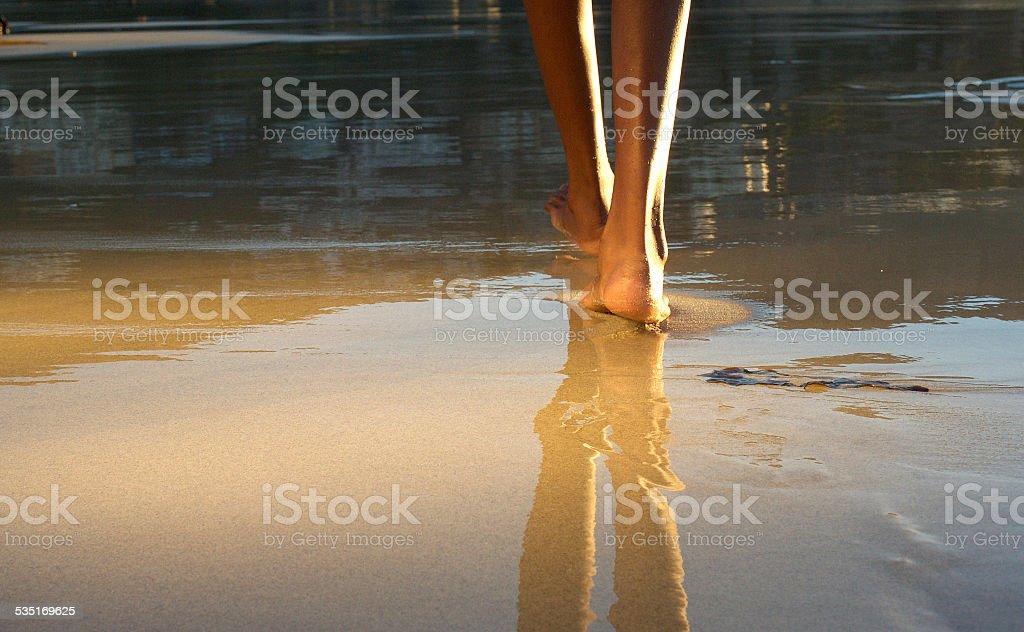 Low angle african american woman walking on beach stock photo