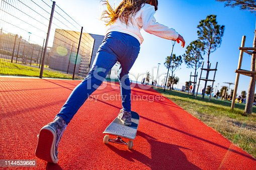 istock Low angle and rear view of a little skateboarding having fun on a playground 1144539660