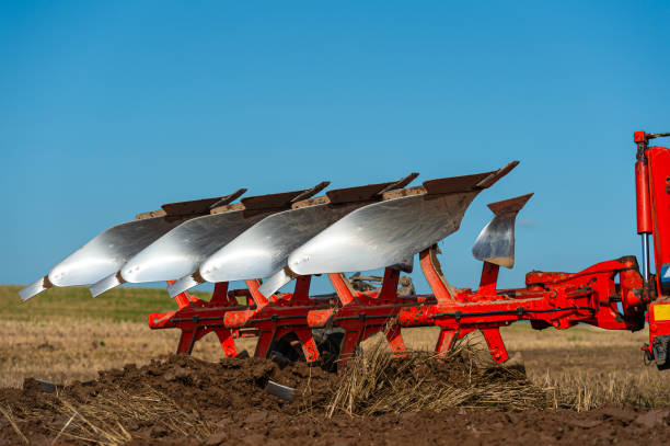 Low angle close up of a plough in action in a field in Dumfries and Galloway south west Scotland A plough being used in late summer to prepare a field and make it ready to sow a new crop to harvest next year johnfscott stock pictures, royalty-free photos & images