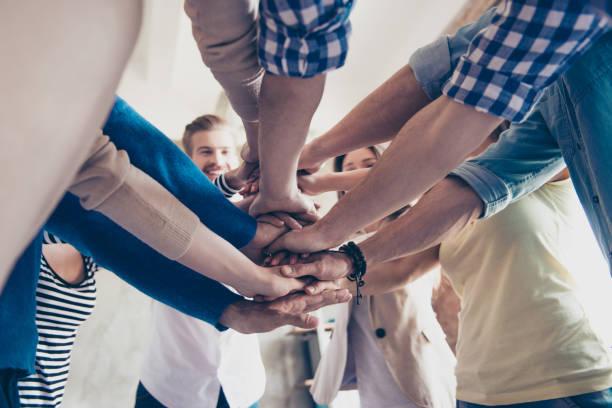 Faible angle recadrée vue de collègues de mettre la main sur le dessus de l'autre, porter des vêtements décontractés. Concept de teambuilding réussi et l'unité - Photo