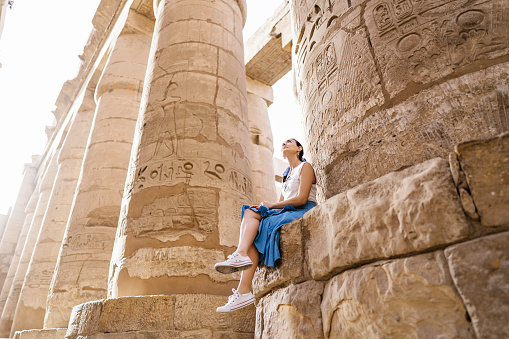 Low angle full length faceless stylish female traveler sitting on stone construction and admiring historic architecture in ancient ruined heritage building with hieroglyphs on weathered columns. Travel concept