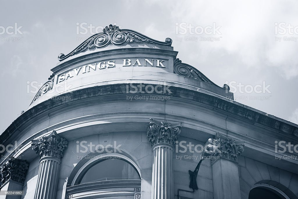 Low angle, gray shaded view of the corner of a savings bank. stock photo