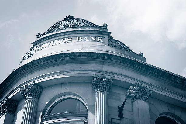 low angle, gray shaded view of the corner of a savings bank. - generic location stock pictures, royalty-free photos & images