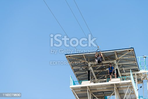 istock Low angle looking up view on zipline tower with worker and African American woman flying and holding to bars handles in Florida Panhandle 1163279830