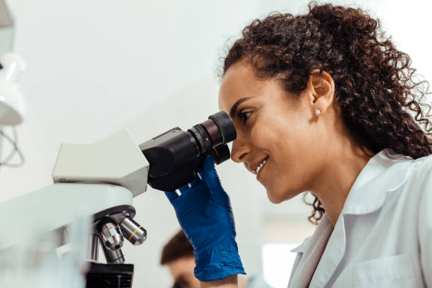 Low angle of a positive female biologist Best job. Low angle of a positive female biologist smiling while enjoying her job microbiologist stock pictures, royalty-free photos & images