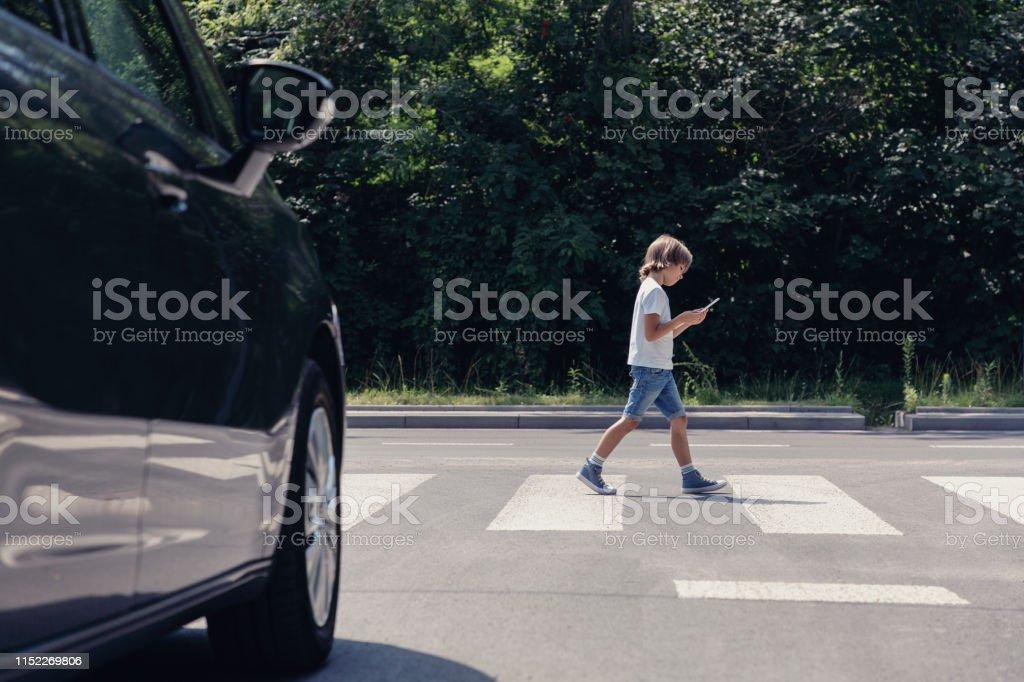 Lage hoek van de auto in de voorkant van voetgangers kruising en wandelen jongen met smartphone - Royalty-free Auto Stockfoto