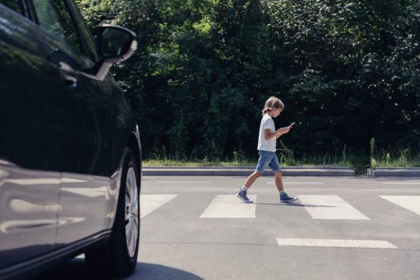 lage hoek van de auto in de voorkant van voetgangers kruising en wandelen jongen met smartphone - oversteken stockfoto's en -beelden