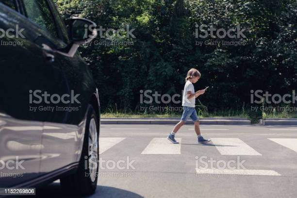 Lage Hoek Van De Auto In De Voorkant Van Voetgangers Kruising En Wandelen Jongen Met Smartphone Stockfoto en meer beelden van Auto