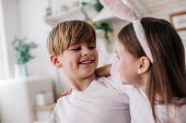 Cropped photo of cute boy looking at girl next to him. He is wearing bunny ears on head. Easter celebrating concept