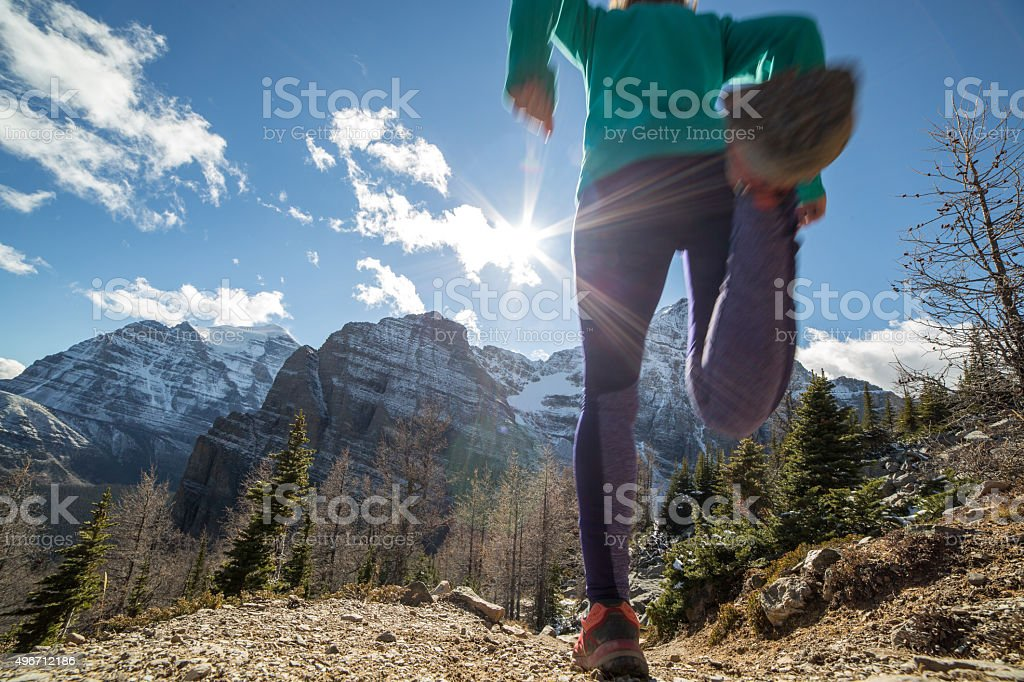 Low angle of woman running downhill towards sunlight stock photo