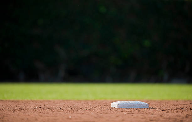 Low angle photo of an empty baseball base Second base and a dark outfield baseball diamond stock pictures, royalty-free photos & images